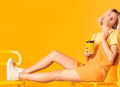 Mulher sentada vestida de amarelo em um fundo amarelo