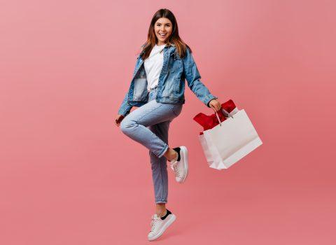 Ofertas Especiais: Moça com uma sacola de compras na mão sorridente e pulando